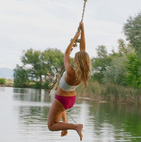 Girl Rope Swinging into Lake