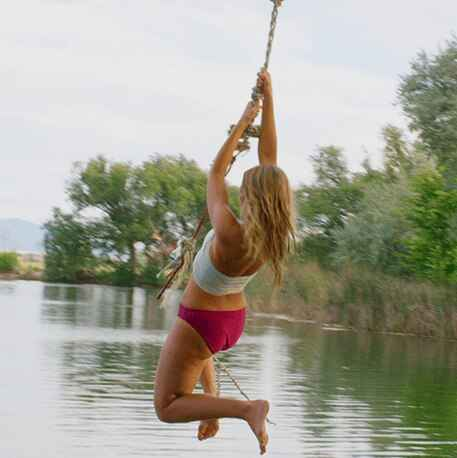 girl swinging from rope