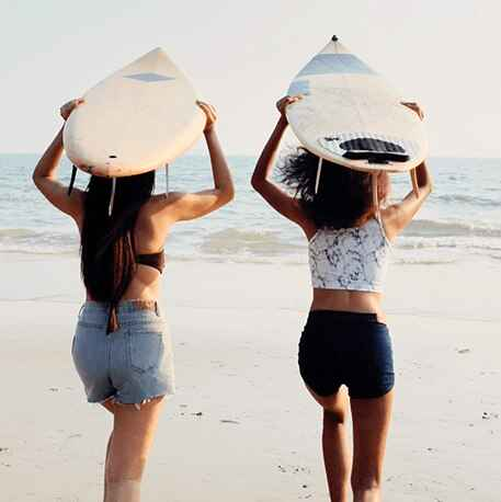girls running towards beach with surfboard