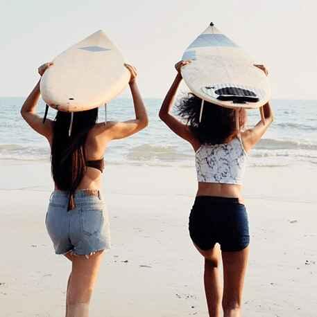 girls running towards beach with surfboard