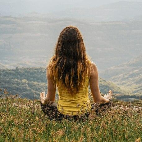 girl meditating on the mountains